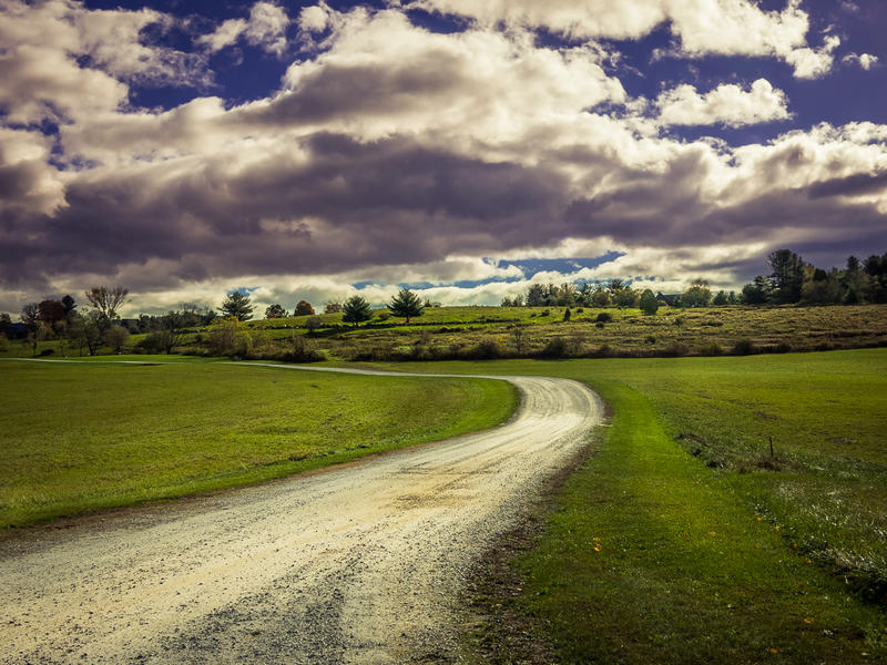 <p>Winding dirt road on a sunny day with big clouds.</p>