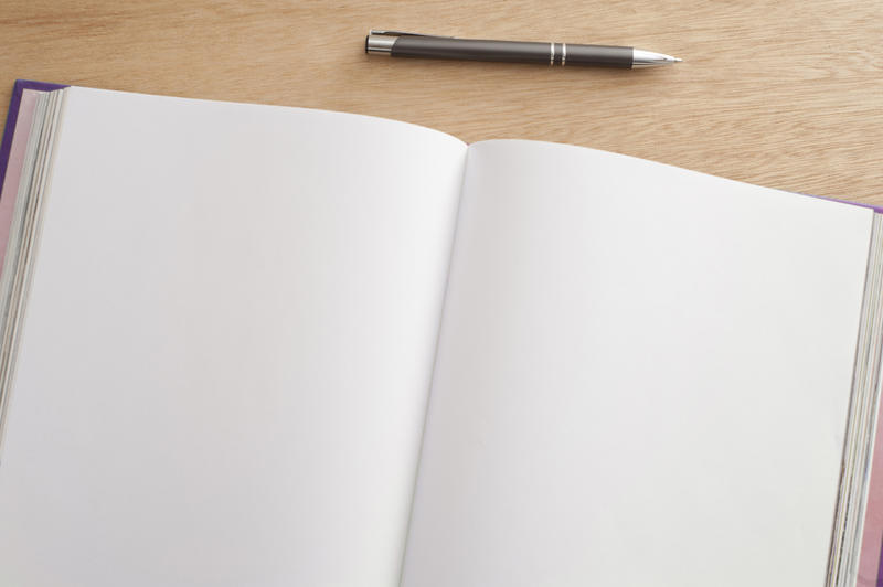 Double spread open blank pages in a journal with a pen above viewed from above on a wooden desk, with copy space