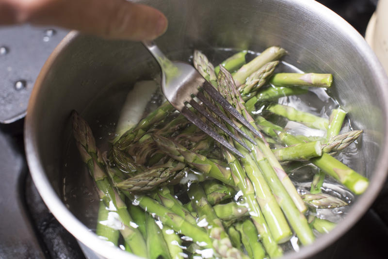High Angle Close Up of Person Cooking Cut Asparagus Spears with Fork in Pot on Stove Top - Unrecognizable Person Boiling Asparagus