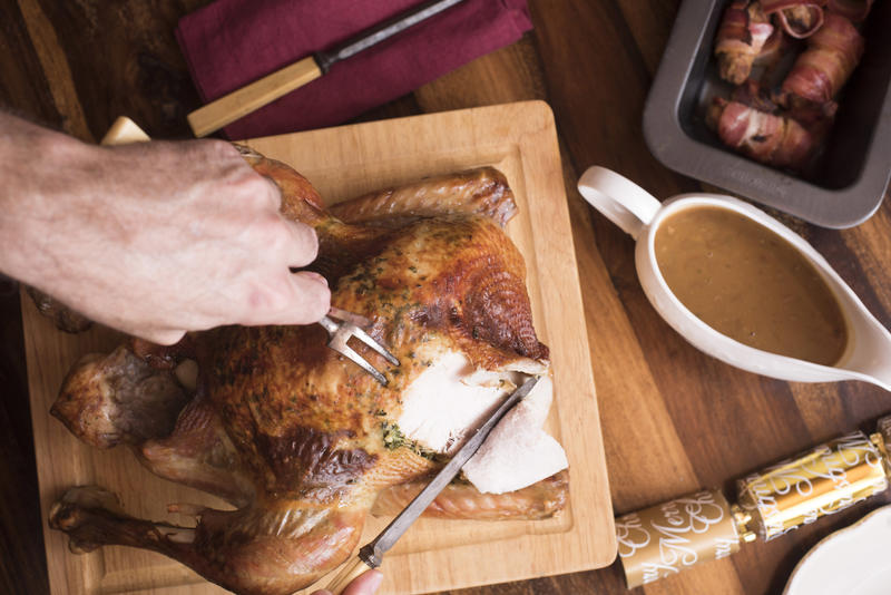 Man carving the Christmas roast turkey for dinner in an overhead view of him slicing breast meat with gravy and bacon rolls alongside