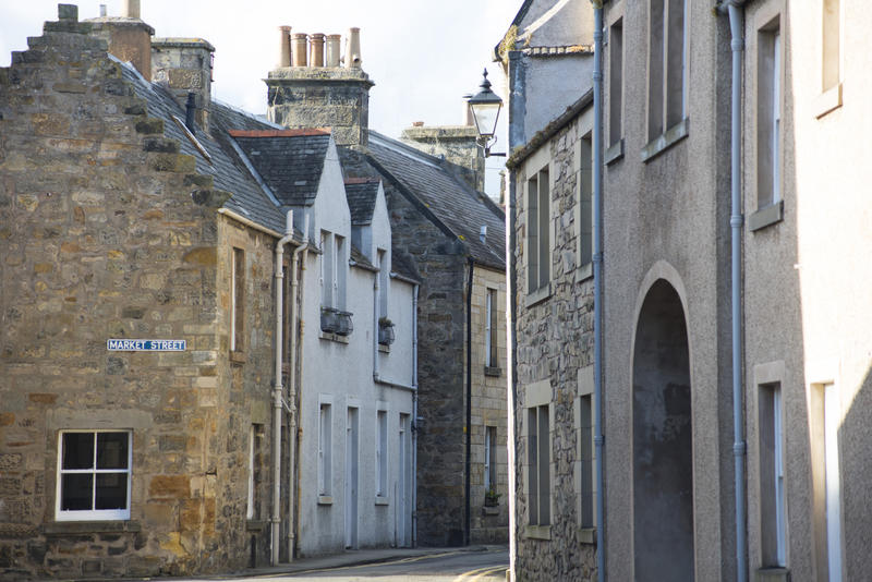 Old two story stone brick homes along tight curved road in Saint Andrews, Scotland