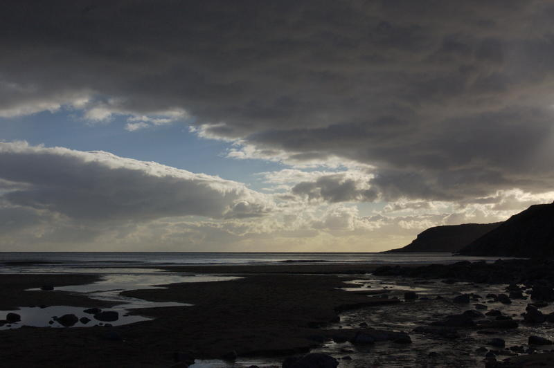 <p>Caswell Bay, in South Wales close to dusk. Shows a coastal stream and the Gower coastline in silhouette<br />