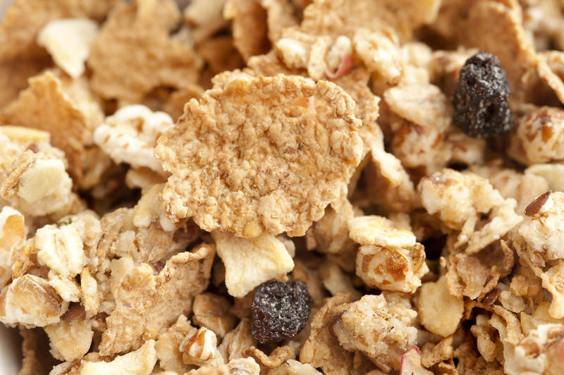Extreme close up on wheat granola breakfast cereal pieces with chopped nuts and little dry raisins