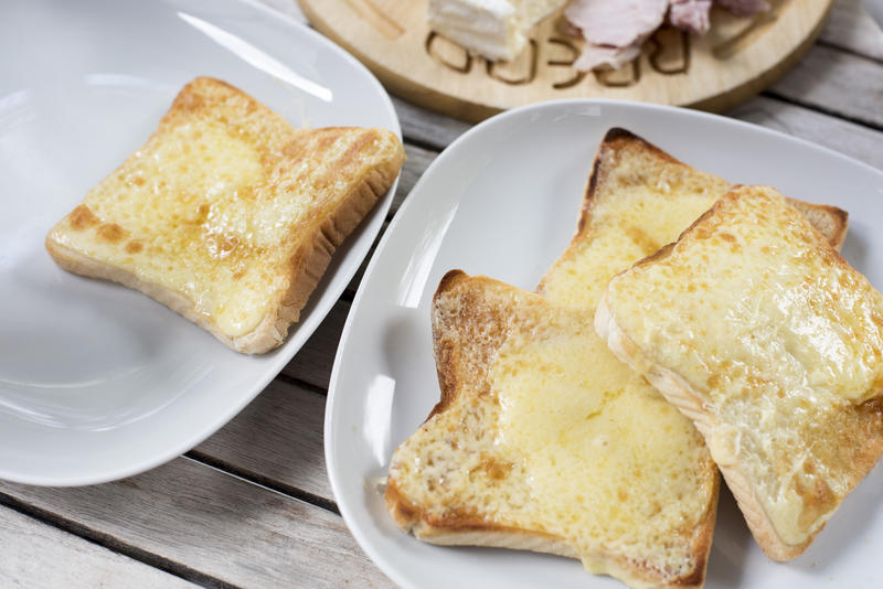 Four square shaped slices of toasted bread and melted mozzarella cheese on top in square plates with round corners