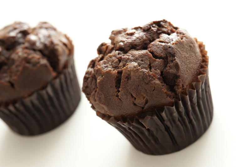 Two homemade delicious chocolate chip muffins with brown cupcake wrapper, oblique close up with copy space