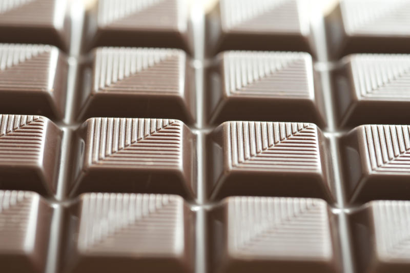Textured bar of chocolate candy viewed at an oblique angle to emphasise the striped pattern, with selective focus