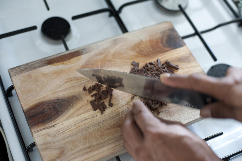 Cooking with chocolate as a cook uses a large sharp knife to chop a bar of chocolate candy on a wooden cutting board