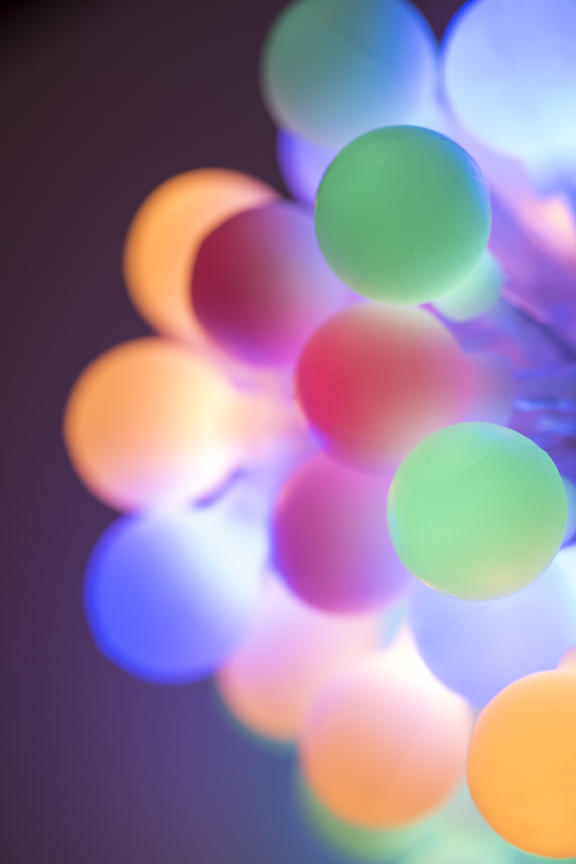 colorful bundle of glowing round christmas lights in pastel or muted coors with shallow dof in