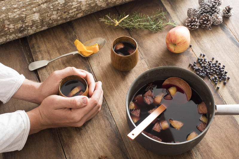 Person warming their hands on a mug of homemade mulled red wine with fresh fruit, herbs and spices surrounding a pot of the spicy aromatic beverage