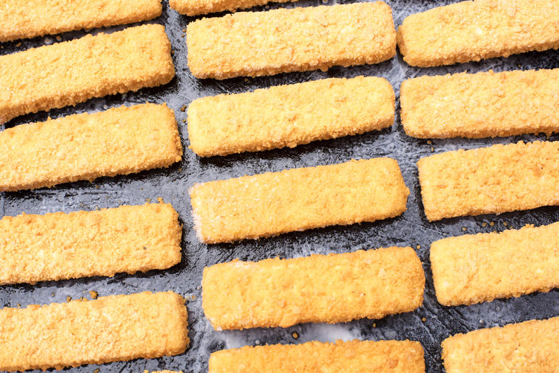 Breaded fish fingers laid out neatly in rows on an baking tray conceptual of convenience and fast food snacks
