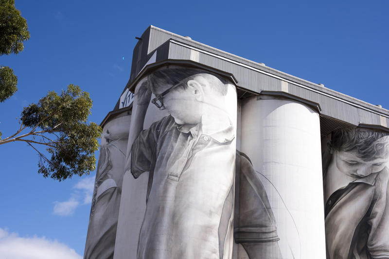 Tall agricultural grain silos at Coonalpyn in South Australia for storing harvested grain and cereal, low angle against a blue sky