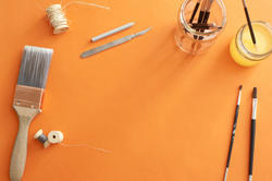 12128   Art Supplies and Paintbrushes on Orange Surface