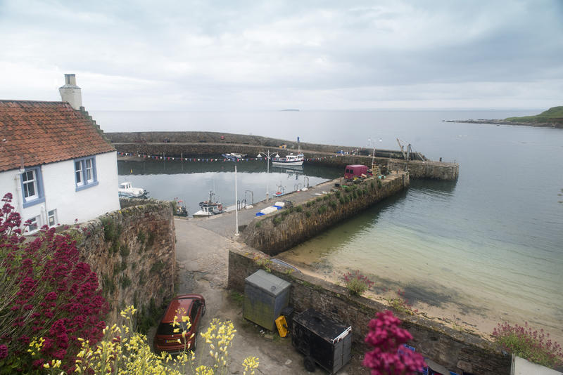 Wide angle view from hillside of Fife Coast harbor under partly cloudy sky in Crail, Scotland
