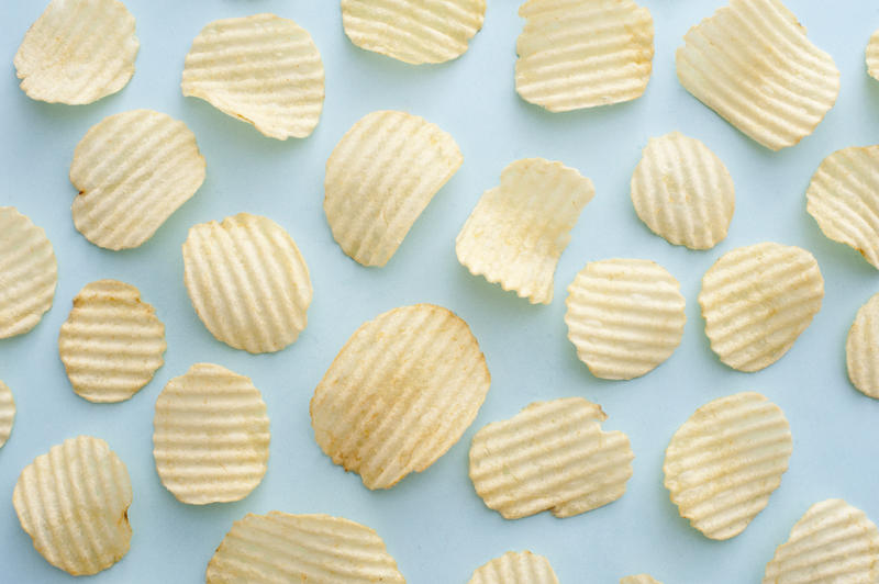 Full background of salty crispy yellow ridged oval shaped potato chips over blue surface