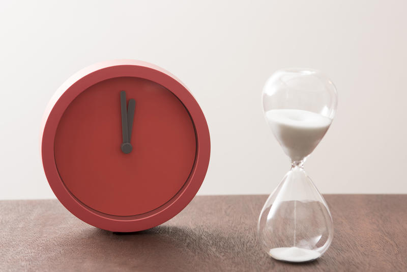 Modern red timer clock and egg timer with running sand in a concept of passing time and countdown to a deadline