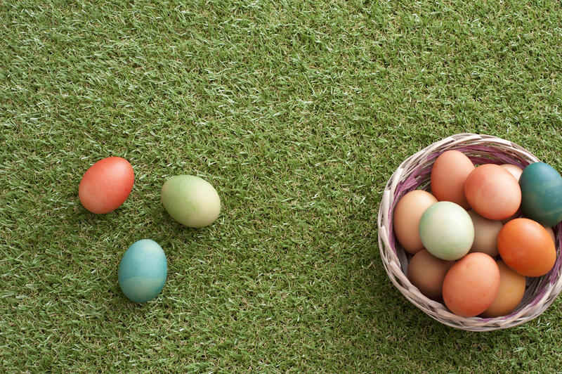 Wicker bowl basket full of dyed Easter eggs with some colored eggs over green loan grass. Easter concept with copy space