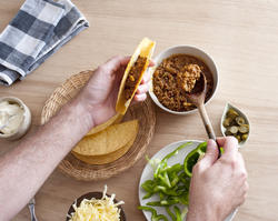 12756   filling a taco shell with ground meat