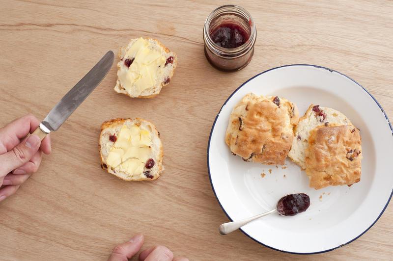 Man preparing fresh scones and jam for tea with a metal plate with two unbuttered scones alongside a halved scone with butter and jar of strawberry jam, overhead view with his hands and knife in view