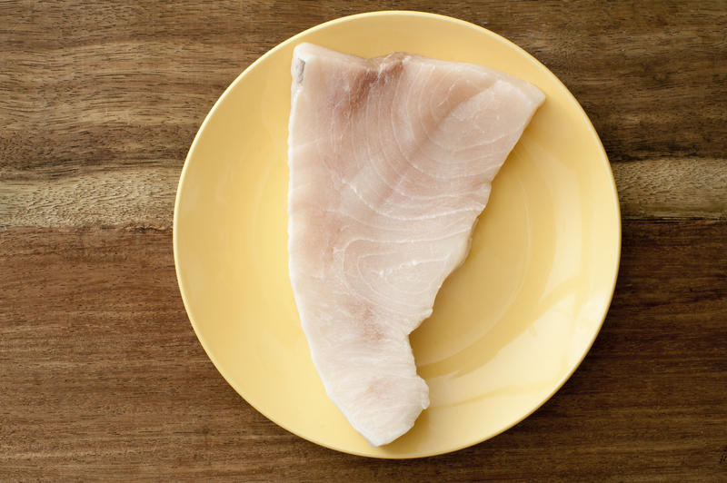 Top down view on raw portion of swordfish steak in simple round plate on brown wooden table surface