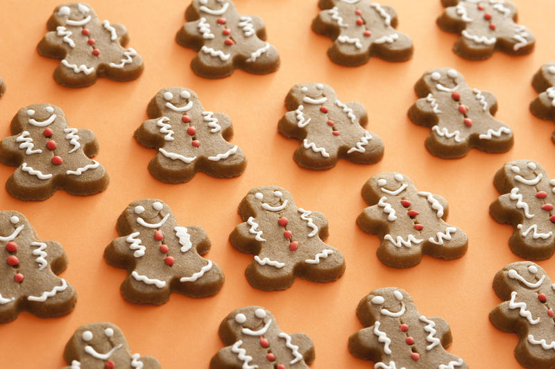 Festive background pattern of gingerbread men laid out on an orange background in neat rows