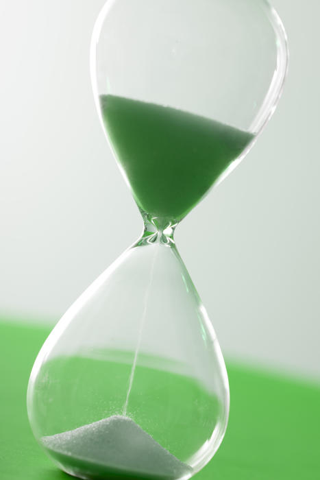 Single glass hourglass timer with pouring sand over green and white background for concept about time