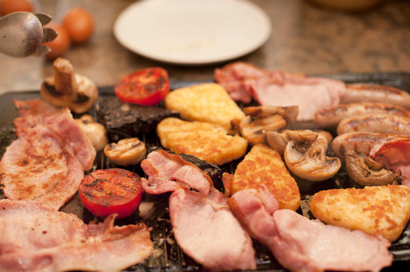 Wholesome English breakfast cooking on the griddle with bacon, hash browns, sausages, tomatoes and mushrooms