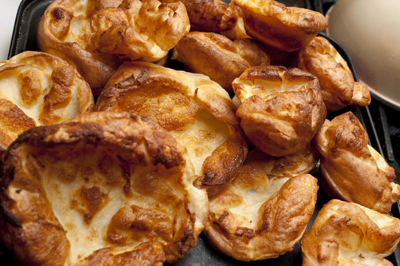 Background of individual small freshly baked homemade Yorkshire puddings ready for serving with a roast meat dish