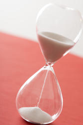 12968   Grains of white sand pouring through an hourglass