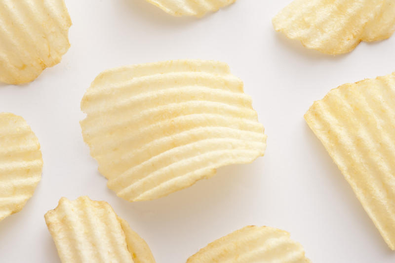 Close up on centered curved ridged potato chip for background about snack or junk food