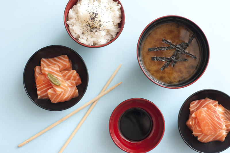 Overhead view of fresh cut and sliced salmon in small bowls beside soy dipping sauce and white rice by soup next to chopsticks against a light blue background