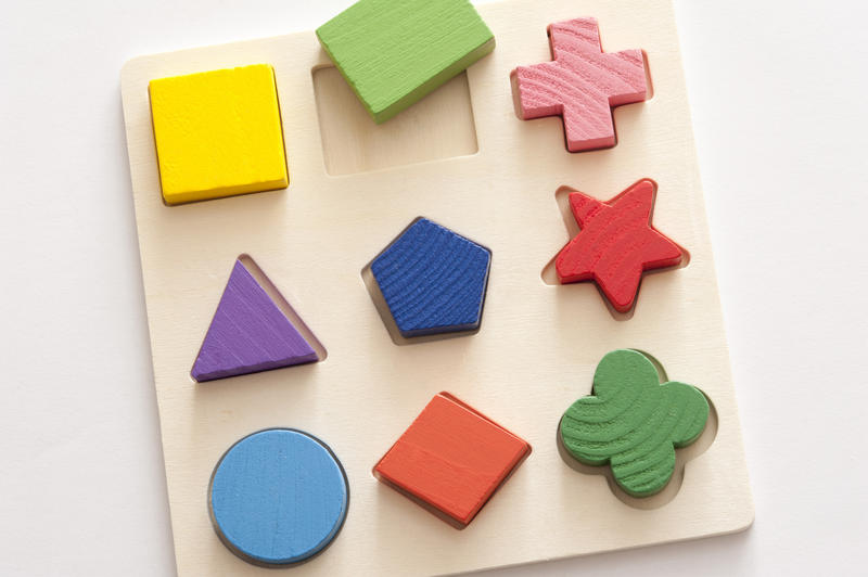 Learning puzzle with nine different colorful basic shapes and cutouts in wood viewed from overhead on white