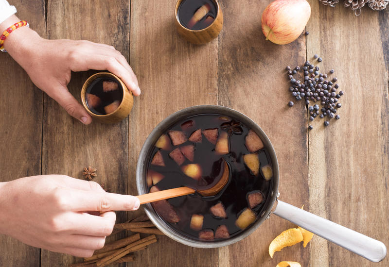 Person serving freshly made mulled red wine with spices and fruit in a pot using a ladle to spoon it into mugs to celebrate the holiday season