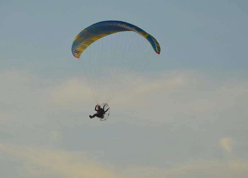 <p>Paragliding over the beach on a sunny evening. Photographed by the sea in Cleveleys near to Blackpool in the UK</p>