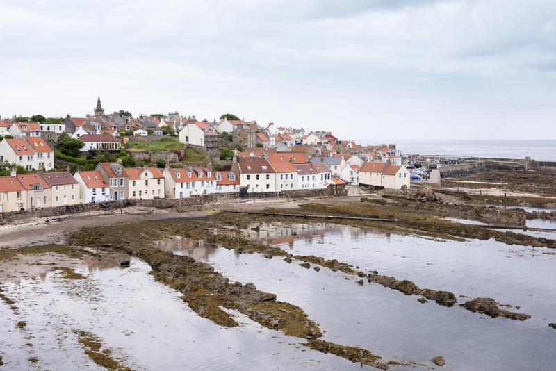 Scene of red roofed houses in Pittenweem Scotland during low tide. Muddy ridges remain where water once stood.
