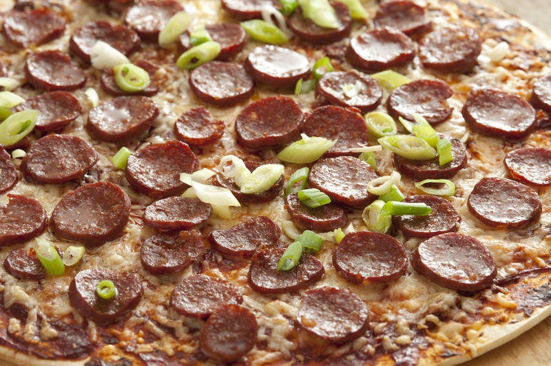 Full background of pepperoni cheese pizza garnished with green scallion onions and peppers