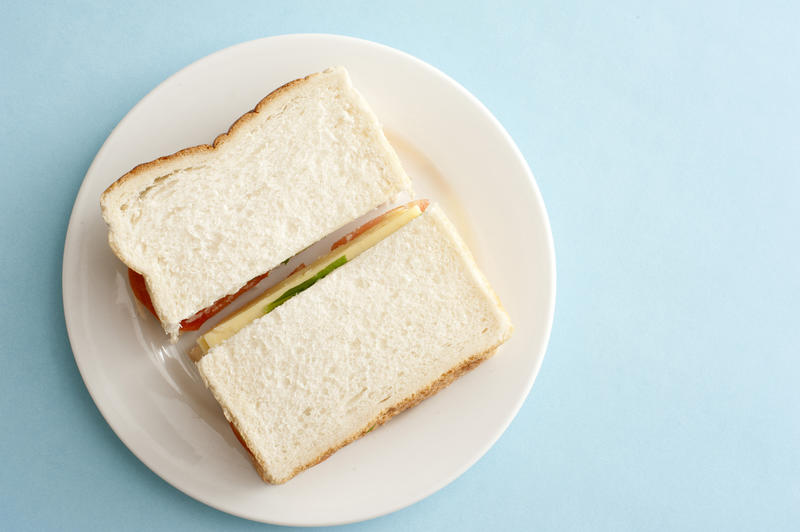 Appetizing white bread sandwich with cheese on a round white plate and against a light blue background as seen from an overhead view