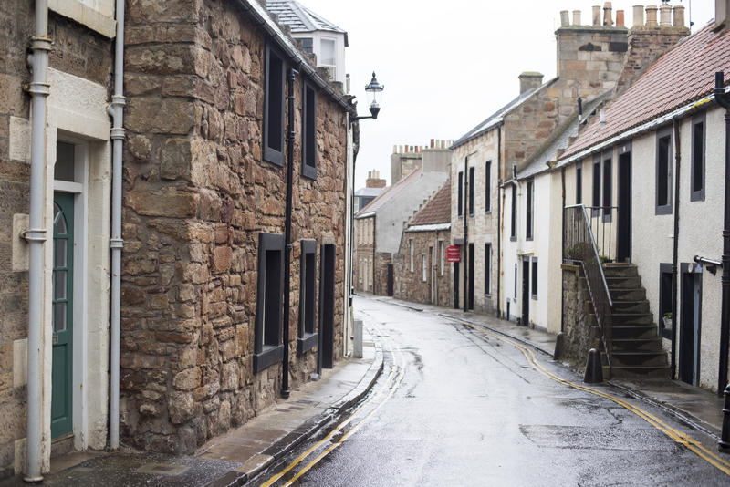 Narrow curved street and sidewalks surrounded by quaint old houses in Cellardyke, Scotland