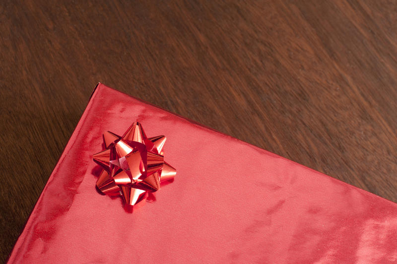 Decorative red gift wrapped box with ribbon bow for Valentines Day, Christmas or birthday over a wooden background, copy space on the present for your wishes or greeting