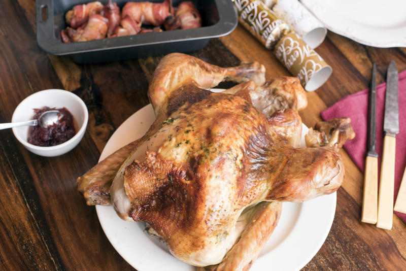 Roast Christmas turkey with accompaniments on a festive holiday table with crackers and carving utensils