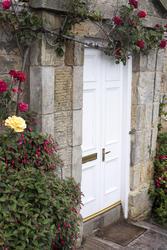 12963   Roses growing around stone block cottage door
