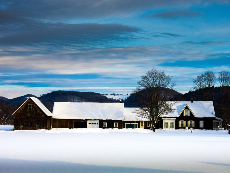 <p>House and barn in Winter at dusk with blue-grey sky, white shadowed snow and shadows on the roof in rural Vermont Woodstock.</p>