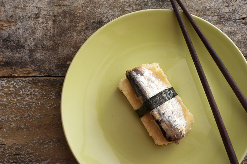 Single serving of sardine fish wrapped with strip of seaweed on plate with brown chopsticks over table