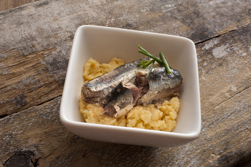 Square white bowl filled with scrambled eggs and raw sardine topped with herbs on rustic wooden table