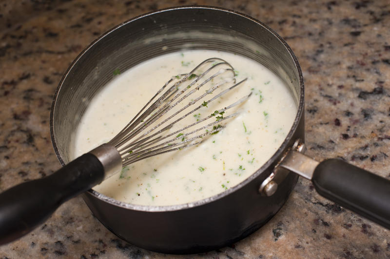 White creamy sauce seasoned with herbs in a saucepan with a metal hand whisk on a granite kitchen counter