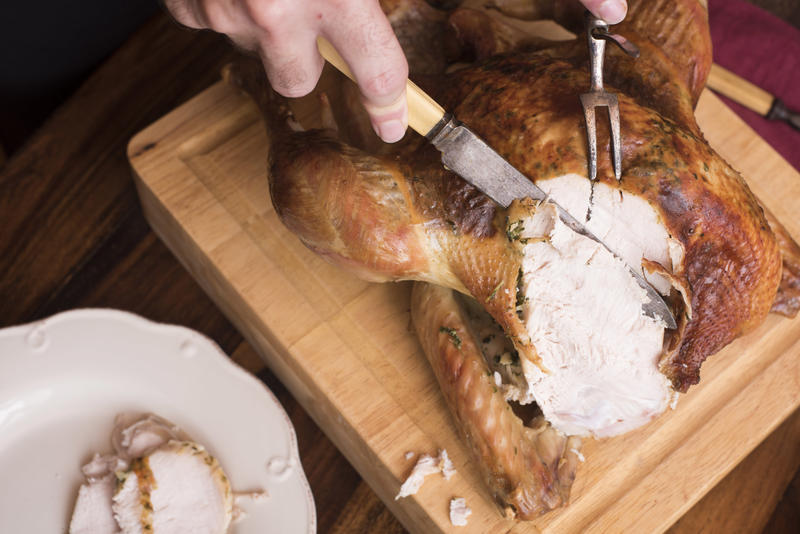 Man slicing a roasted Christmas turkey with vintage bone-handled utensils and placing it onto plates for serving