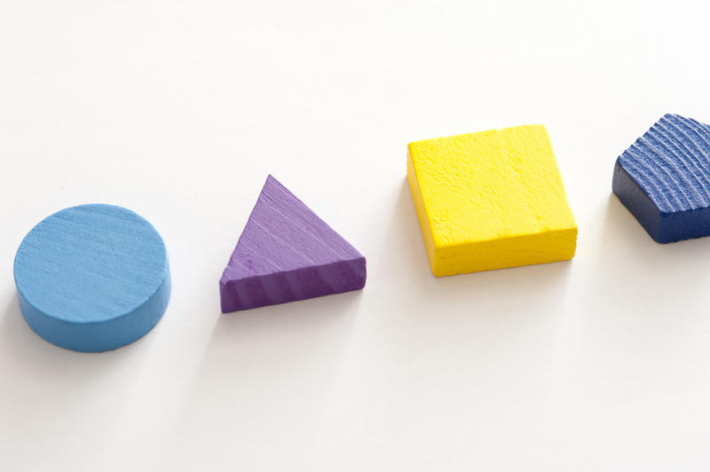 Four basic colorful wooden shapes showing a circle, triangle, square and pentagon in a line on white for educating young children, with copy space