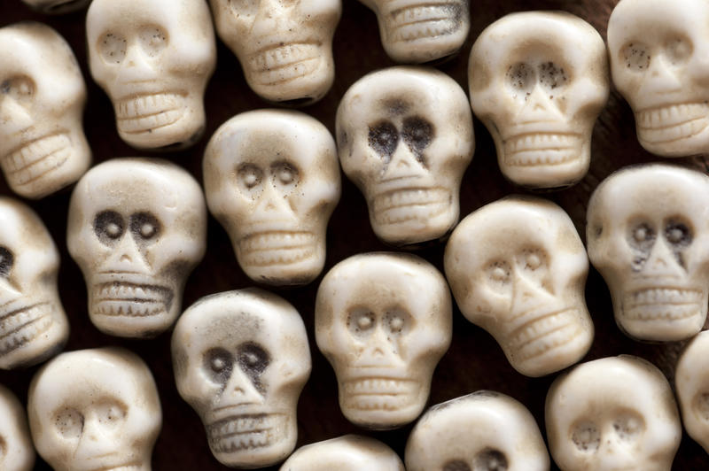 Background of white plastic toy skulls in a neat arrangement viewed from above for Halloween or horror themes