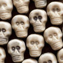 12786   Background of white plastic toy skulls