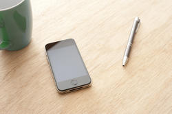 13738   Smartphone on table with pen and mug