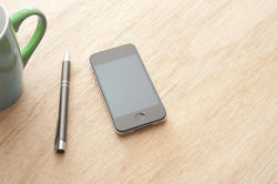 13721   Smartphone with pen on wooden table